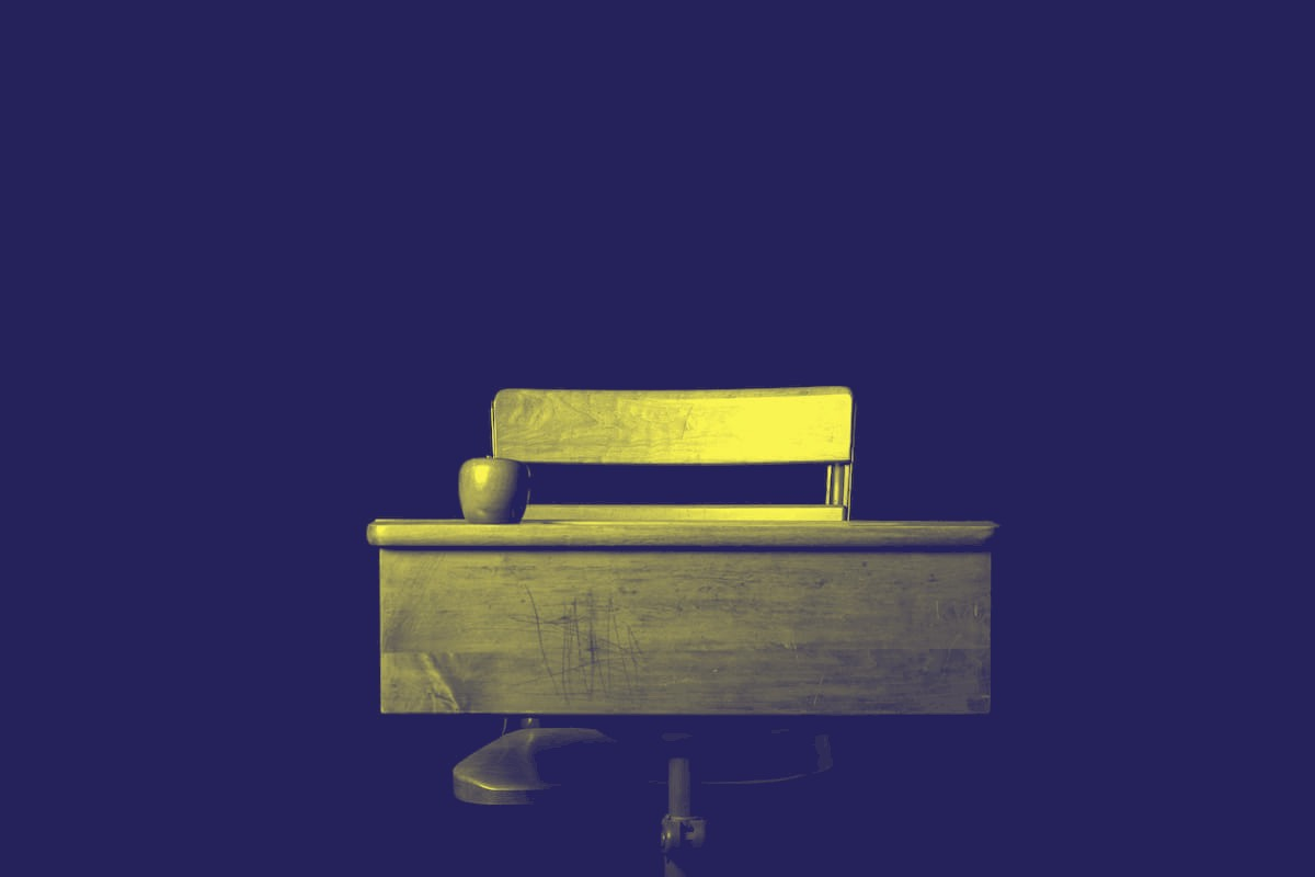 an old-fashioned school desk and chair with an apple