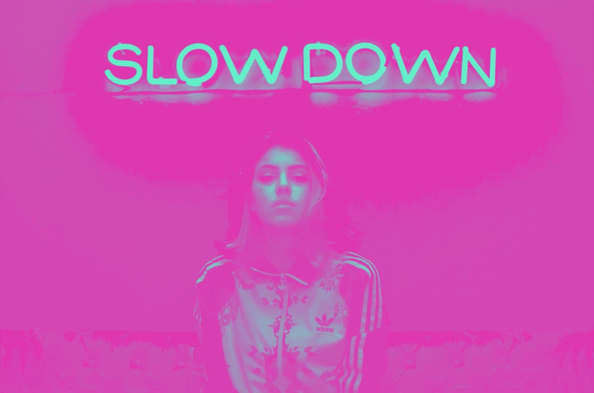 a woman in a training jacket under a neon sign saying 'slow down'
