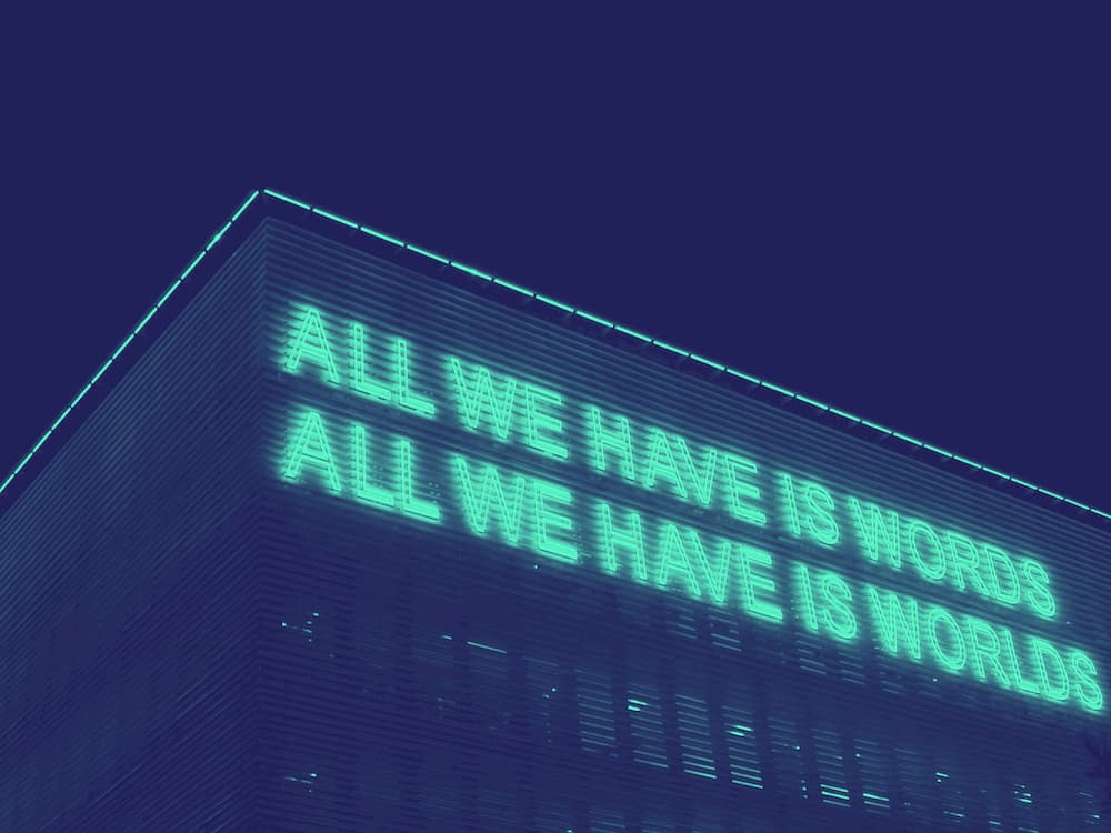 "Neon sign reading: ""All we have is words / all we have is worlds"""