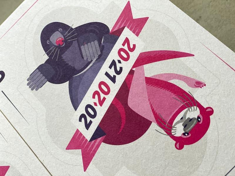 """Postkarte, die wie eine Spielkarte gestaltet ist. Man sieht links oben einen violetten Maulwurf, rechts unten einen pinkfarbenen Fischotter. Dazwischen ein Band, auf dem die Jahreszahlen """"2020"""" und """"2021"""" diagonal dargestellt sind."""