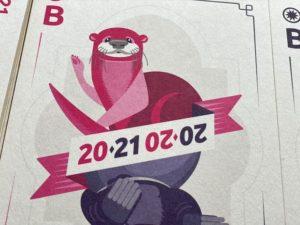 """Der Fischotter-Teil der Postkarte, die wie eine Spielkarte gestaltet ist. Man sieht oben einen pinkfarbenen Fischotter. Darunter ein Band, auf dem die Jahreszahlen """"2020"""" und """"2021"""" diagonal dargestellt sind."""