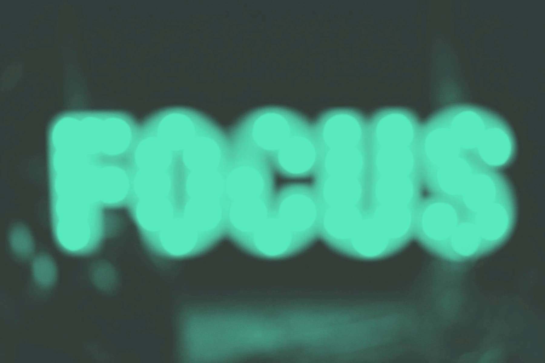 A blurry image of the word 'focus' in green in front of a dark grey backdrop
