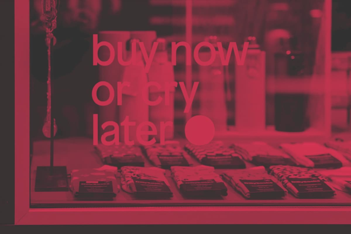 a shop window in red/grey duotone. The window sticker says 'buy now or cry later'.