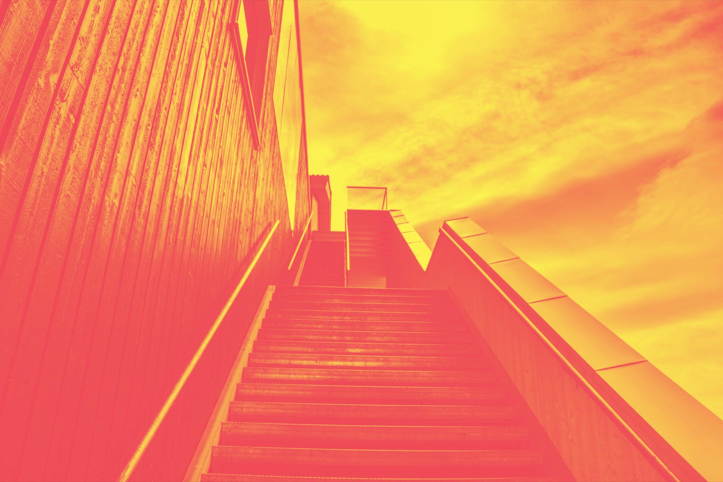 Treppe, die seitlich an einem Gebäude hinaufführt. Gelb-rotes Duotone-Bild.