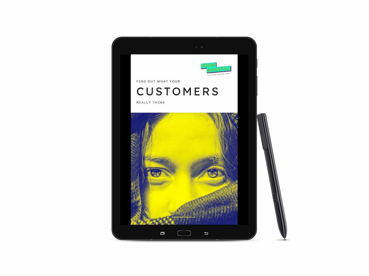Samsung Galaxy tablet showing the cover of the ebook: From Scratch logo, name of the ebook and a yellow/navy duotone closeup image of a young woman looking directly at the viewer. Her lips and chin are hidden beneath a scarf.