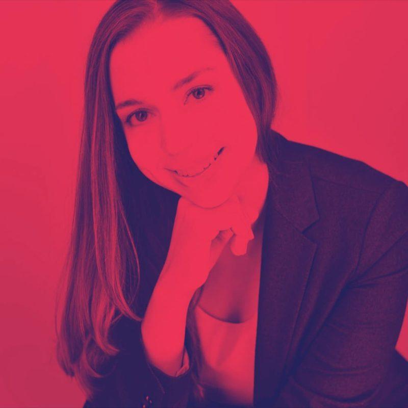 katharina gross schaut in die Kamera und stützt das Kinn in die Hand. Sie trägt langes dunkles Haar, einen dunklen Blazer und ein helles T-shirt.