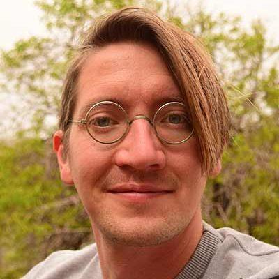 Gerrit Schuster schaut direkt in die Kamera. Er trägt eine runde Brille, ein graues T-Shirt, Dreitagebart und einen asymmetrischen Haarschnitt.